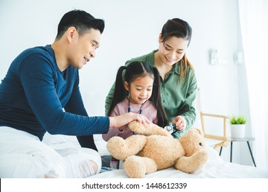 Future little daughter playing doctor consulting with Parents sitting on bed and happy family having fun together