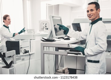 Future of medicine. Waist up of positive professional laboratory scientists using modern equipment and pointing at screen while expressing interest to work
