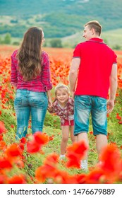 A future mom in a checkered red shirt and jeans walks with her daughter and husband in a poppy field among flowers. View from back