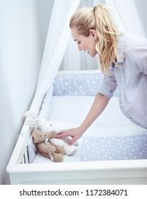 Future mom prepares child's room, happy young pregnant female with pleasure decorating crib with soft toys, new life concept