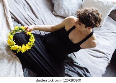 Future mother sits on a bed. The pregnant woman , in a black dress
