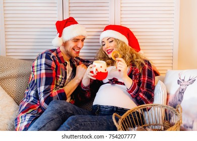 Future parents in the hat of Santa Claus on a sofa eating cookies