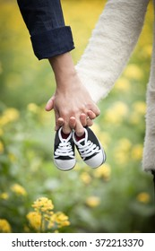 Future parents holding hands and a pair of little shoes over blur yellow flowers background. Concept of Parents-To-Be.