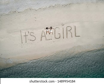 """Future parents resting on the white sand of the beach by the turquoise waters enjoying anticipation, """"It's a girl"""" written on the sand; aerial view."""