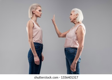 Future and past. Old grey-haired woman with bob haircut showing stopping gesture to serious good-looking girl