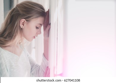 Future perspective and outlook. Pretty girl or young woman with blond, long hair and cute face leaned against window frame on sunny day, copy space