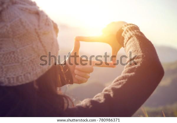 Zukunftsplanung, Nahaufnahme von Händen, die Rahmengesten mit Sonnenaufgang auf dem Berg machen, Weibliche fangen den Sonnenaufgang, Sonnenlicht im Freien.