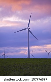 Future Power - Sunset. Wind Turbines Plantation Vertical Photography. Power Industry Theme. Technology Photo Collection.