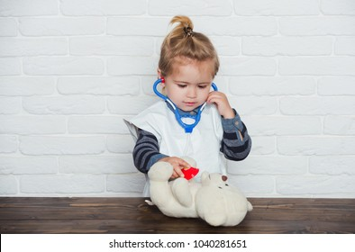 Future profession concept. Baby veterinarian examine toy animal with stethoscope. Game, development, imagination. Childhood, playroom, nursery. Child play doctor with teddy bear on white wall.