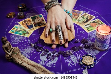 Future reading concept. Divination. Fortune teller female holding in hands a deck of Tarot cards and a mandala with astrological zodiac signs in background. Mystique, astrology mandala.