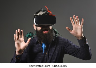 Future technology, 3d technology, virtual reality, journey to past - happy bearded man in virtual reality goggles traveling in jurassic park. Jurassic period. Era of dinosaurs. Man with toy dinosaurs.