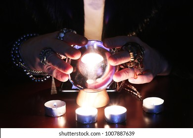 Future teller guessing on a glass ball with candles