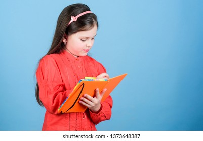 Future writer having literature class. Adorable small child writing literature report. Cute little girl holding book in English literature. Book and literature promotion programme, copy space.