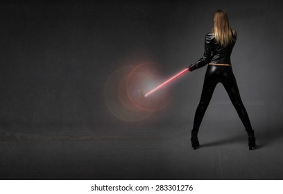 futurisitc soldier with weapon on hand, dark background