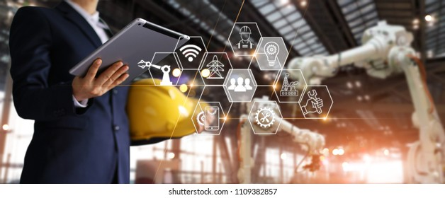 A futuristic architect, Businessman, Engineer manager using tablet with icon network, Industrial robotics, Automation robot arms machine in intelligent construction site. Industry technology concept