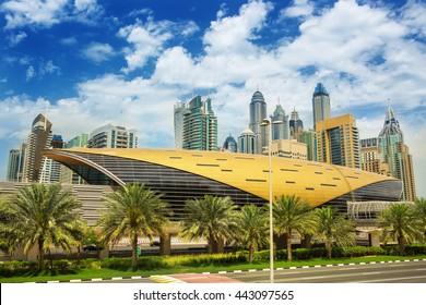 Futuristic building of Dubai metro station and luxury skyscrapers behind in Dubai Marina,United Arab Emirates