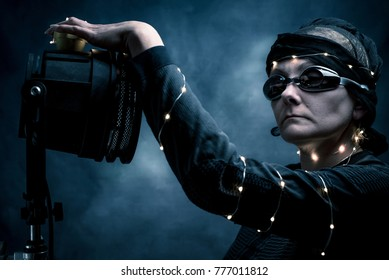 futuristic, dark image of a woman who stands next to an old movie lamp. She is dressed in black, her hair is shawl and lights, she wears dark glasses