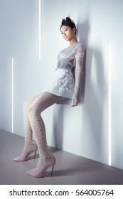 Futuristic fashion young woman. Beautiful young multi-racial asian caucasian model cyber girl in silver urban clothes with conceptual hairstyle and make-up against modern interior in full lenght. Sci