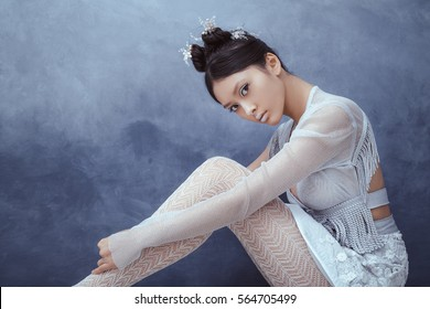 Futuristic fashion young woman. Beautiful young multi-racial asian caucasian model cyber girl in silver urban clothes with conceptual hairstyle and make-up sitting against textured blue wall. Sci-fi
