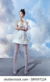 Futuristic fashion young woman. Beautiful young multi-racial asian caucasian model cyber girl in silver urban clothes with conceptual hairstyle and make-up against blue sky and clouds in full lenght