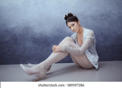 Futuristic fashion young woman. Beautiful young multi-racial asian caucasian model cyber girl in silver urban clothes with conceptual hairstyle and make-up sitting against textured blue wall in full
