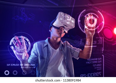 Futuristic gadget. Clever creative child visiting IT courses and wearing virtual reality glasses for making a program