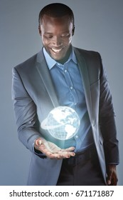 Futuristic global business concepts, innovative modern technology virtual reality globe held by black businessman in suit
