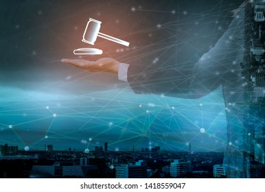 Futuristic hands of businessman holding hammer icon and information on online auctions,cityscape background,Concept Internet Of things(IOT), advanced technology in the auction via wireless networks
