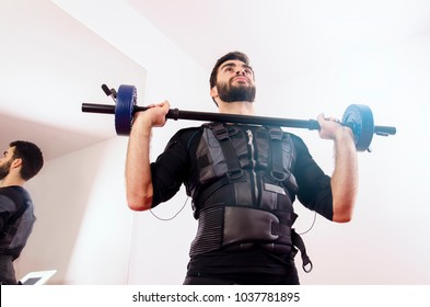 Futuristic image, man exercising with EMS suit on, view from below
