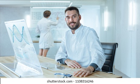 In the Futuristic Laboratory Male Scientists Smiling into Camera. He is Working with DNA Structure Shown on the Transparent Display Computer. In the Background Female Scientists Writing on Blackboard.