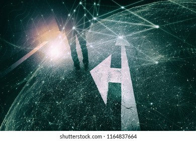Futuristic man stands alone on ashpalt road with intersection arrows signs on the floor. Conceptual business people cyberspace network sphere background.