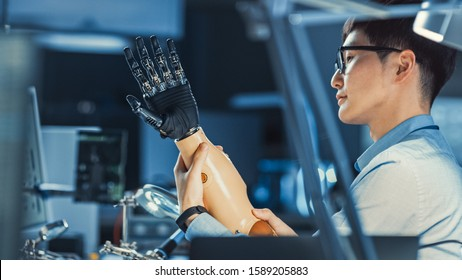 Futuristic Prosthetic Robot Arm Being Tested by a Professional Japanese Development Engineer in a High Tech Research Laboratory with Modern Computer Equipment.