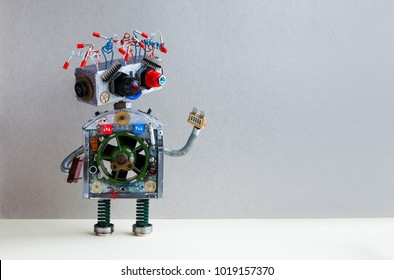 Futuristic robot electrical wire hairstyle, plug arm. Creative design robotic toy mechanism, funny head, colored blue red eyes. Copy space, gray wall background.