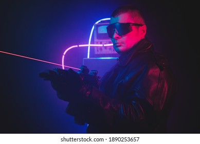 Futuristic soldier in the neon lights with the rifle.