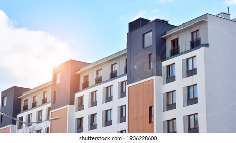 Futuristic square architecture of apartment building. Real estate with panoramic windows and blue sky with clouds.