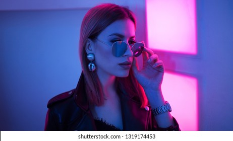 Futuristic style portrait in blue and purple light. Fashion portrait of trendy young woman in leather jacket, Pink color light on a background and her face