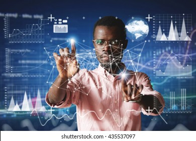Futuristic technology. Double exposure. Portrait of African employee in glasses, looking at the camera with serious concentrated expression, touching screen interface against high-tech interior