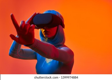 Futuristic woman in VR helmet scrolling invisible screen while interacting with virtual reality under neon light against bright orange background