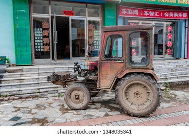 Fuyang/China 08.10.2019: the Old, dismantled tractor on a city street, in front of the local store.