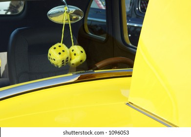 Fuzzy dice in a customized vehicle on display at a car show.