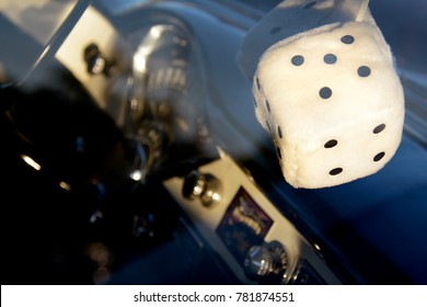 Fuzzy Dice Dangling from Classic Car Rearview Mirror with Dashboard