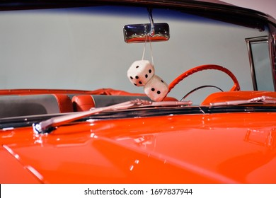Fuzzy Dice hang in the window of an Orange Classic Convertible Car