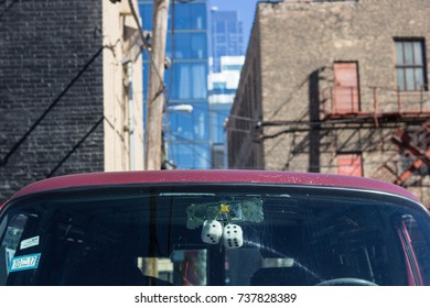 Fuzzy dice hanging from a mirror in a truck in a city