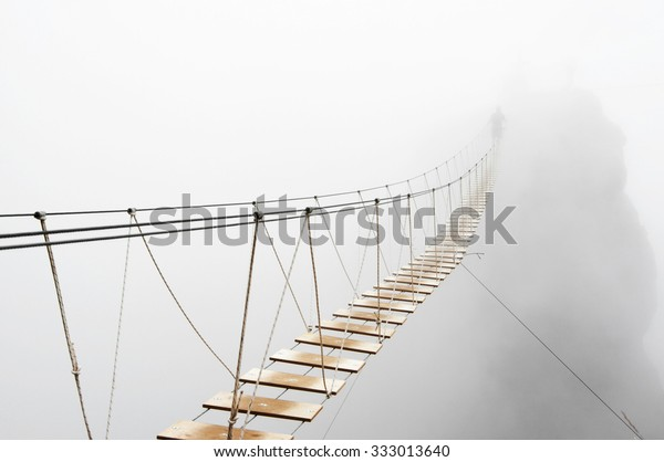 Fuzzy man walking on hanging bridge vanishing in fog. Focus on middle of bridge.