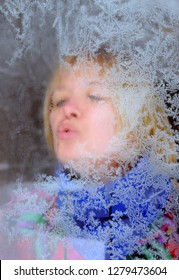 Fuzzy portrait of Caucasian woman through the frosty window in the winter