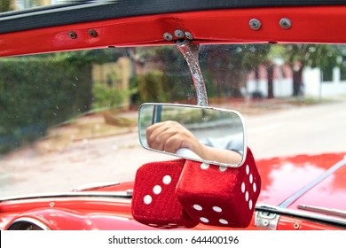 Fuzzy red dice hang on rear view mirror on Havana classic car