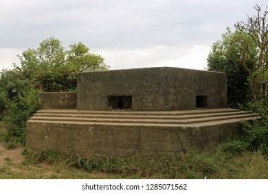 An FW3/22 type world war two pillbox on the east coast of England with two loopholes and surrounded by trees and shrubs with a grey blue sky.