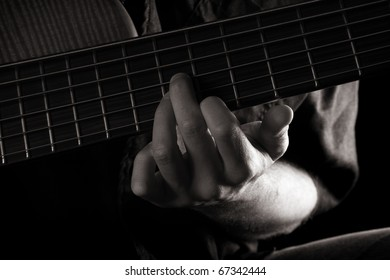 G major chord on six-string electric bass guitar (left hand), toned monochrome image