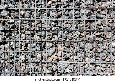 Gabion Made Of Black Stone And Metal Wire Mesh. A stone wall that uses metal and stone in harmony. Ecology friendly using a natural resources for construction. Mesh for blocking the collapsing stone