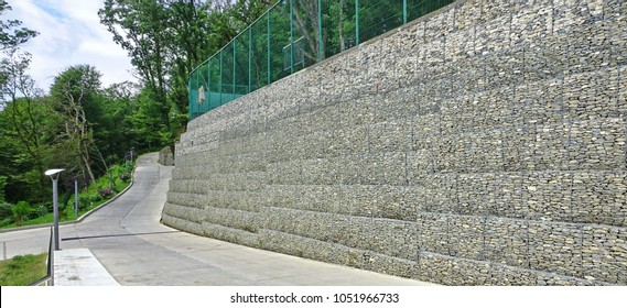 Gabion Protective Wall Filled With  Rocks And Stones And Tied With Thick Metal Wire.  Landscape With Blue Sky And Trees Near The Concrete Road